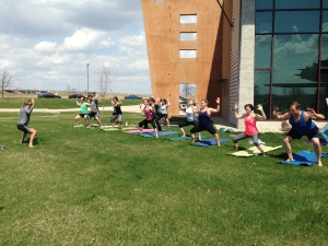 Johnson Fitness employees participate in yoga on the front lawn.